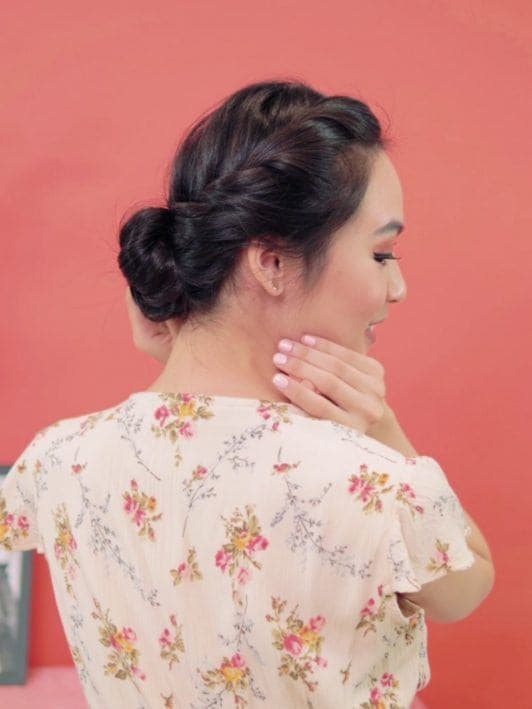 French rope braid updo: Back side of an Asian woman showing off her French rope braid updo with a smile