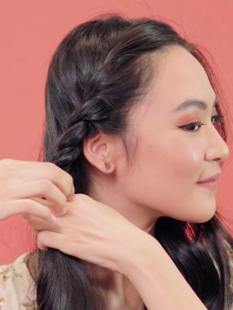 Asian woman twisting her hair from her crown to the side