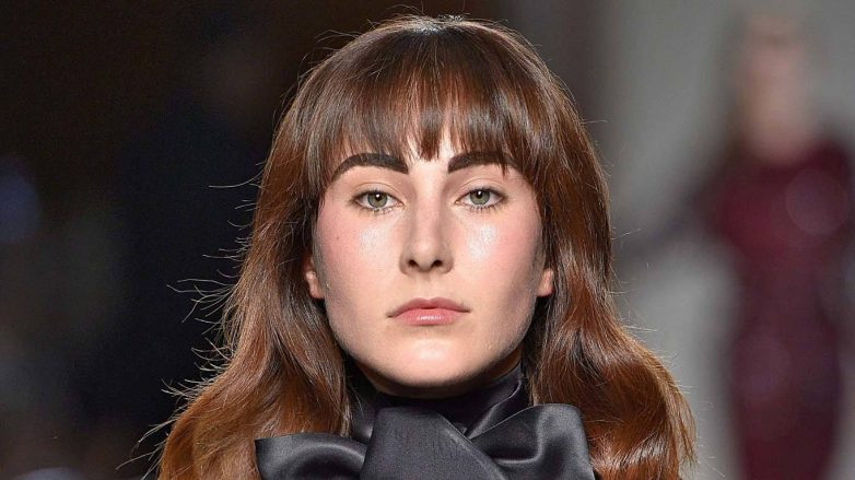 Hair color maintenance: Woman with brown hair with bangs walking on the runway