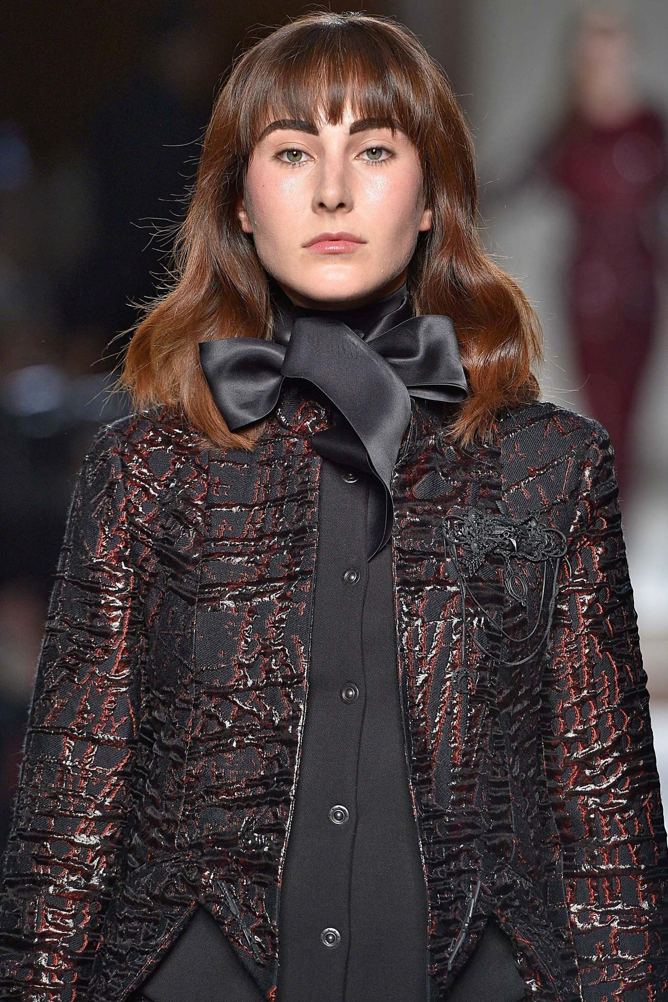 Model with chocolate brown shoulder-length hair with bangs wearing a jacket