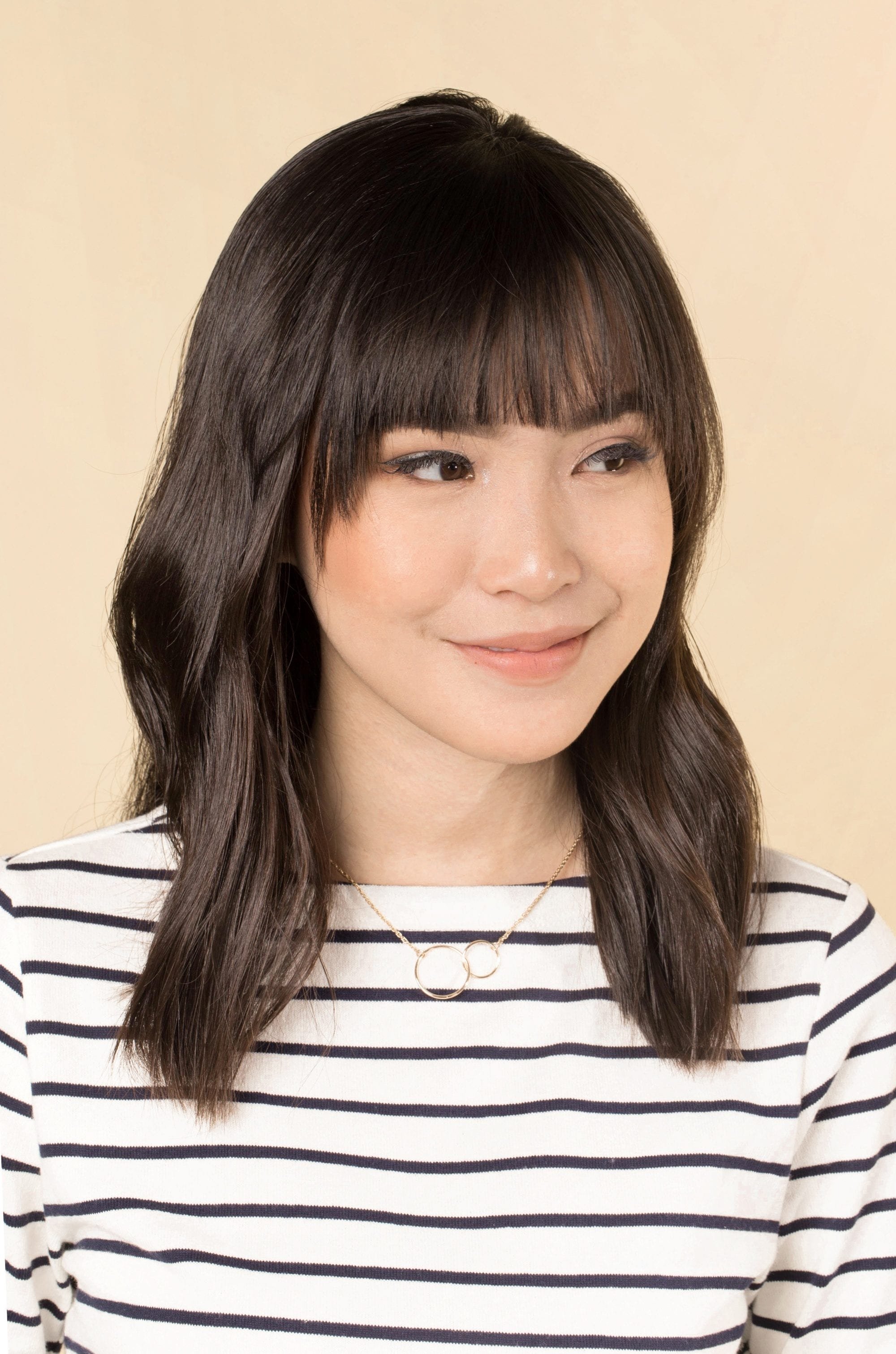 Asian woman with dark shoulder length hair with bangs wearing a striped shirt