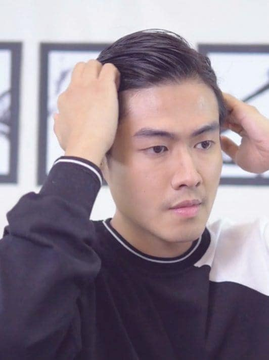 How to style men's hair without heat: Asian man parting his hair on one side