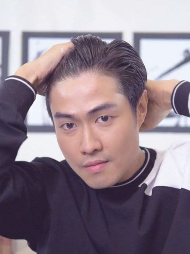 How to style men's hair without heat: Asian man applying putty on his hair