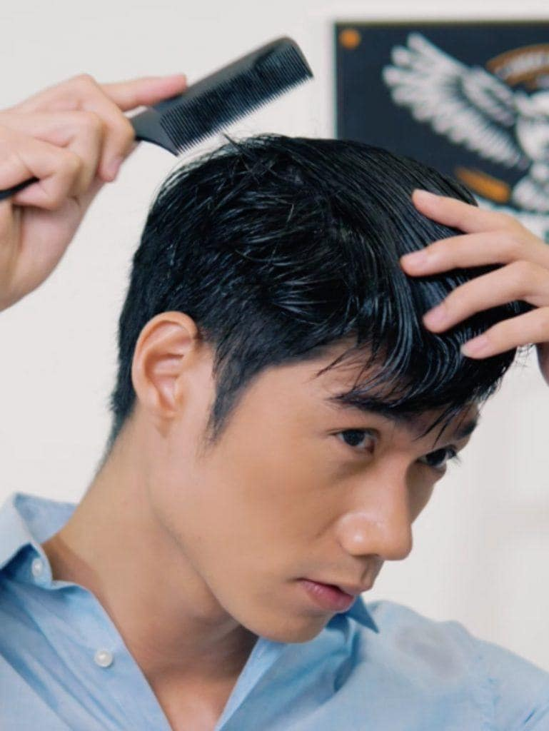 How to style textured bowl cut for men: Asian man combing his hair with a fine tooth comb