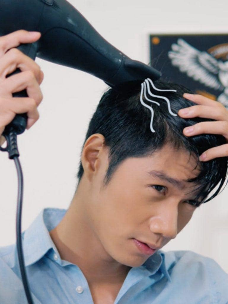 How to style textured bowl cut for men: Asian man blow drying his hair with a blow dryer