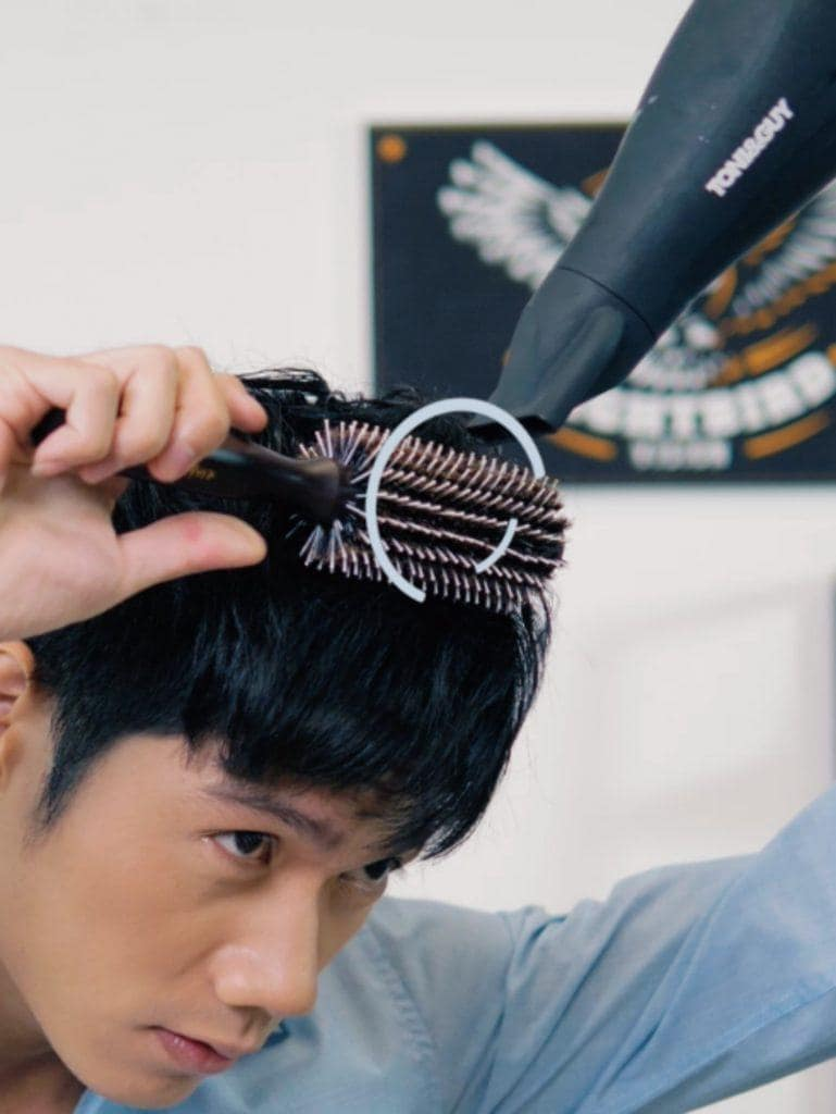 How to style textured bowl cut for men: Asian man blow drying his hair while brushing it in c motion