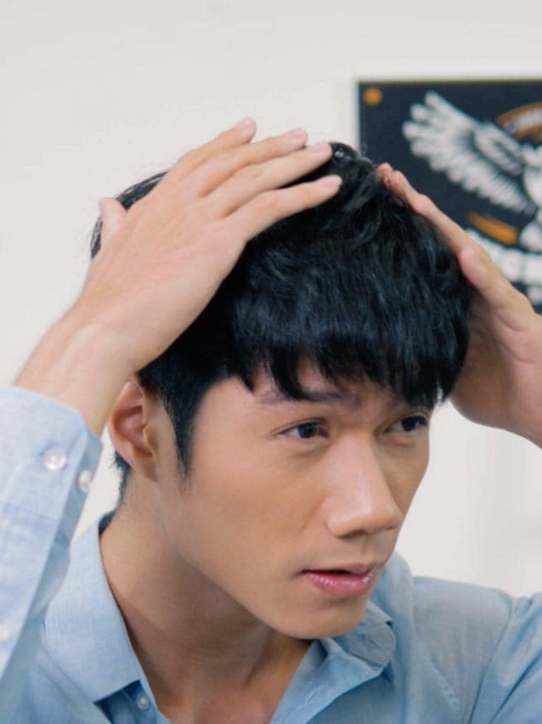 How to style textured bowl cut for men: Asian man applying putty on his textured bowl cut