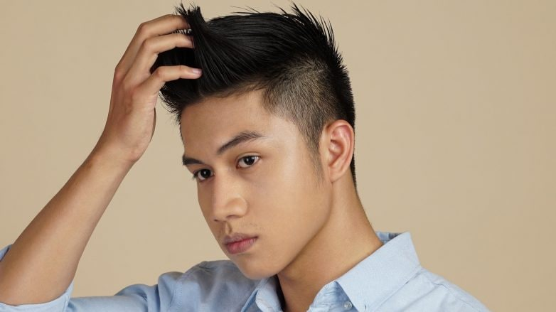 Asian man wearing a blue polo touching his hair to show itchy scalp causes