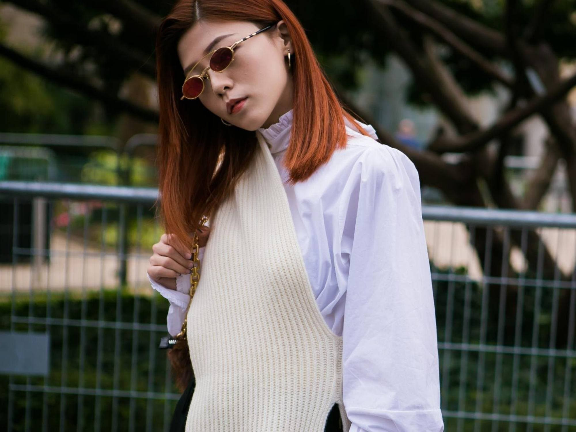 Woman with natural copper hair in white top and shades