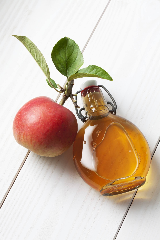 Natural dandruff remedies: an apple beside a bottle of apple cider vinegar