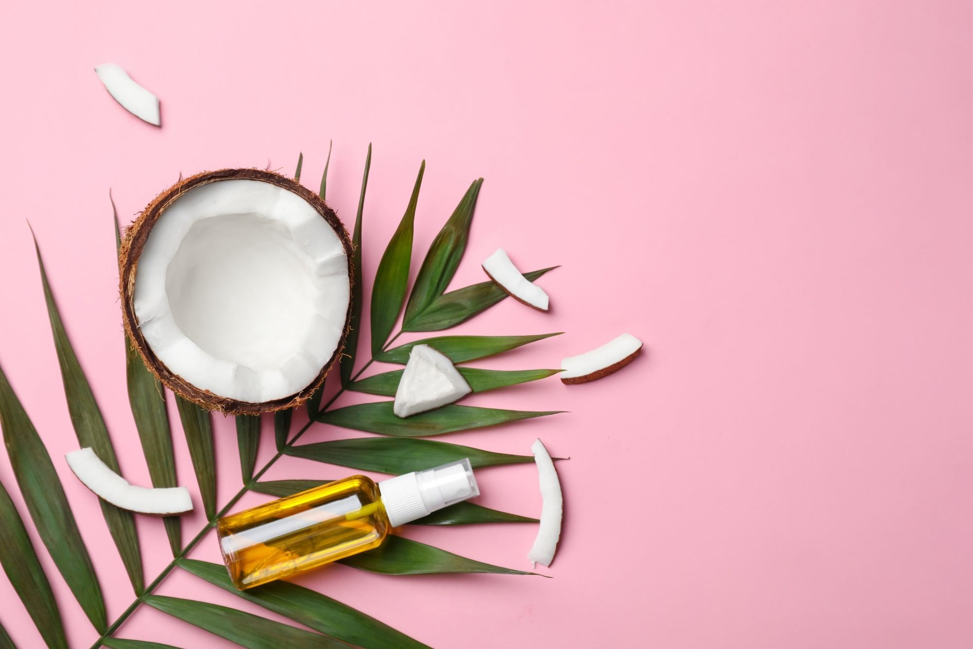 Natural dandruff remedies: a half of a coconut with a bottle of its oil