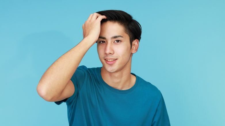 Natural dandruff remedies: Asian man in a blue shirt combing his hair with his fingers