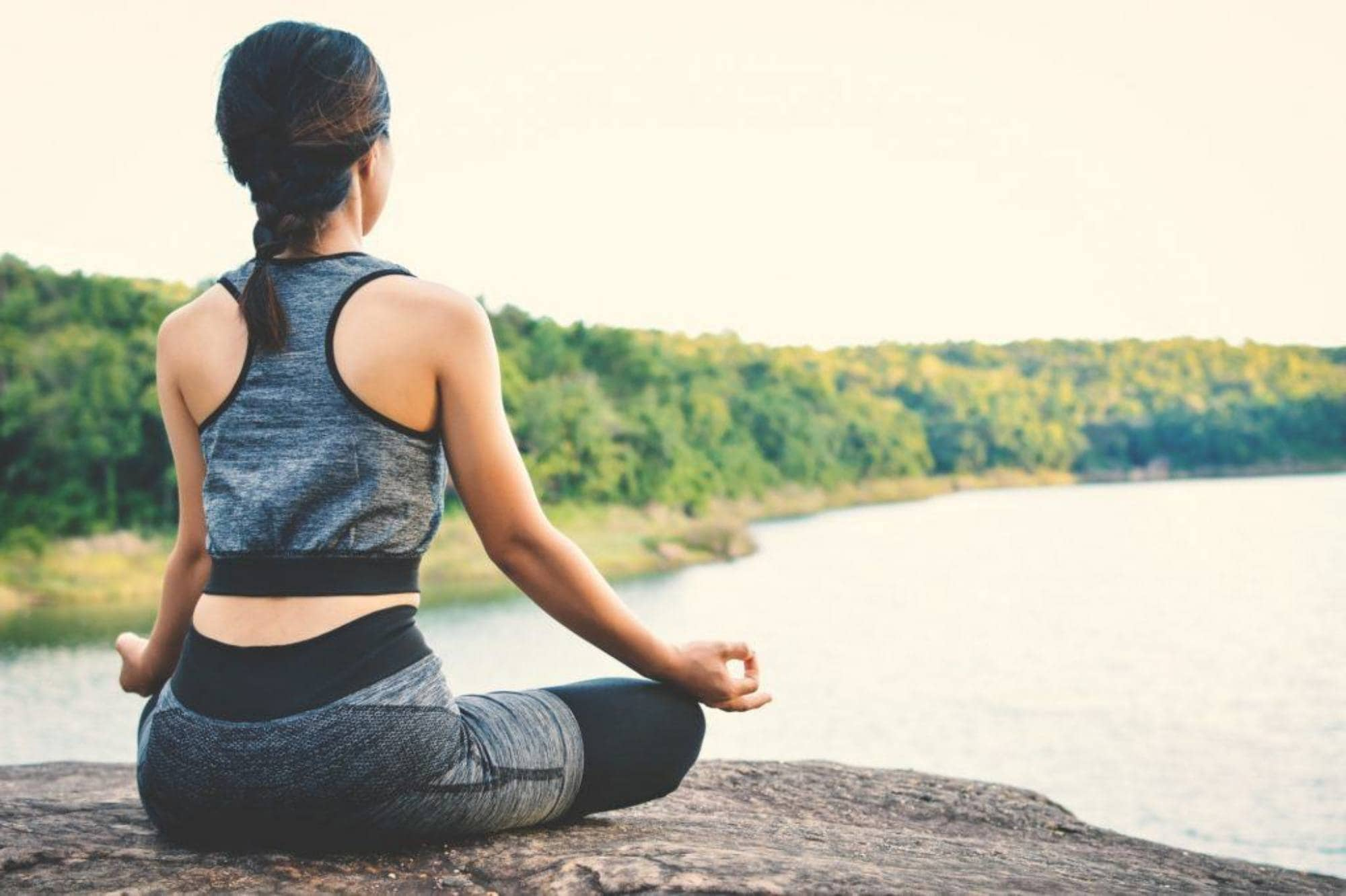 Natural dandruff remedies: a girl meditating by the beach