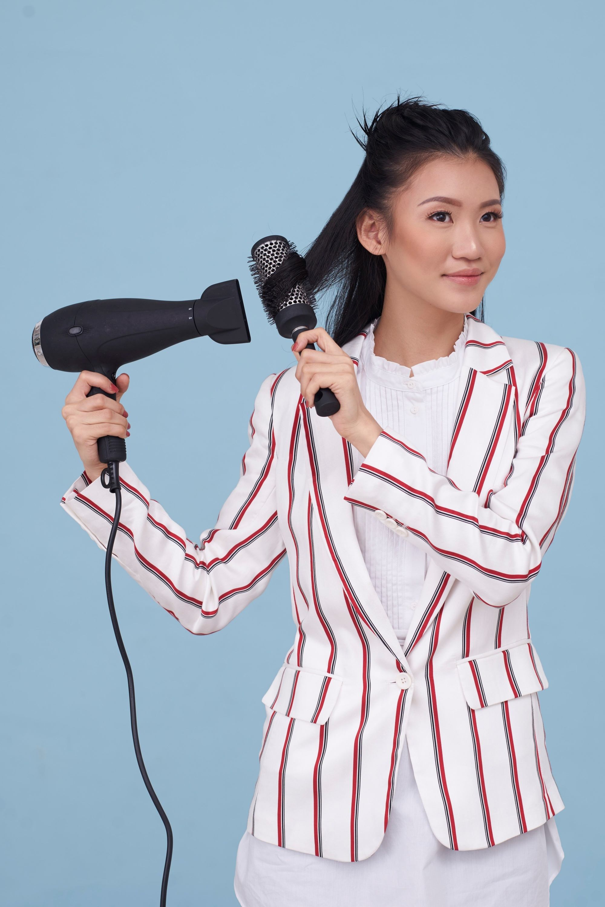 Asian woman wearing a striped blazer blow drying her hair to straighten it