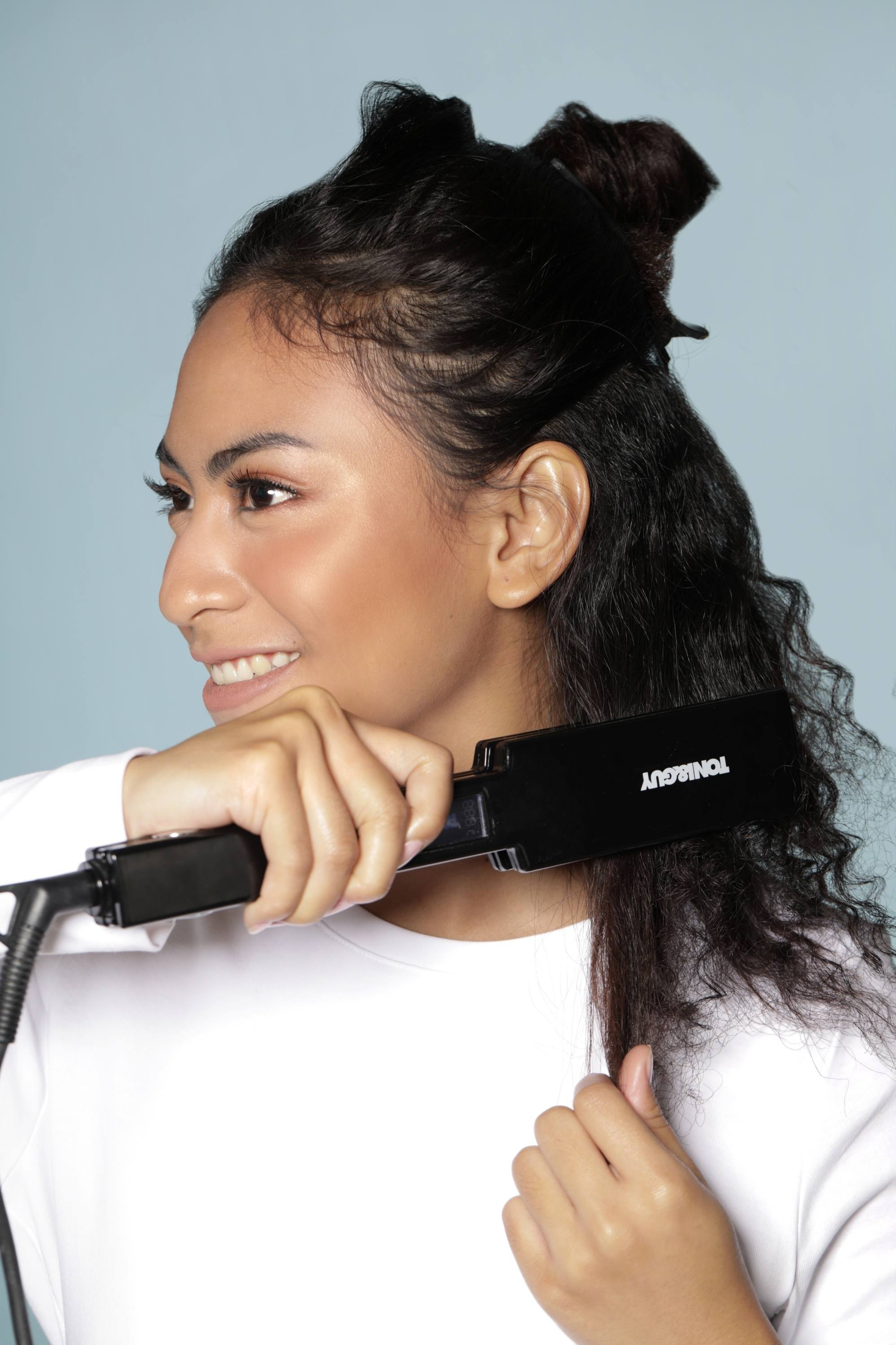 Natural hair straightener:: Asian woman straightening her dark curly hair