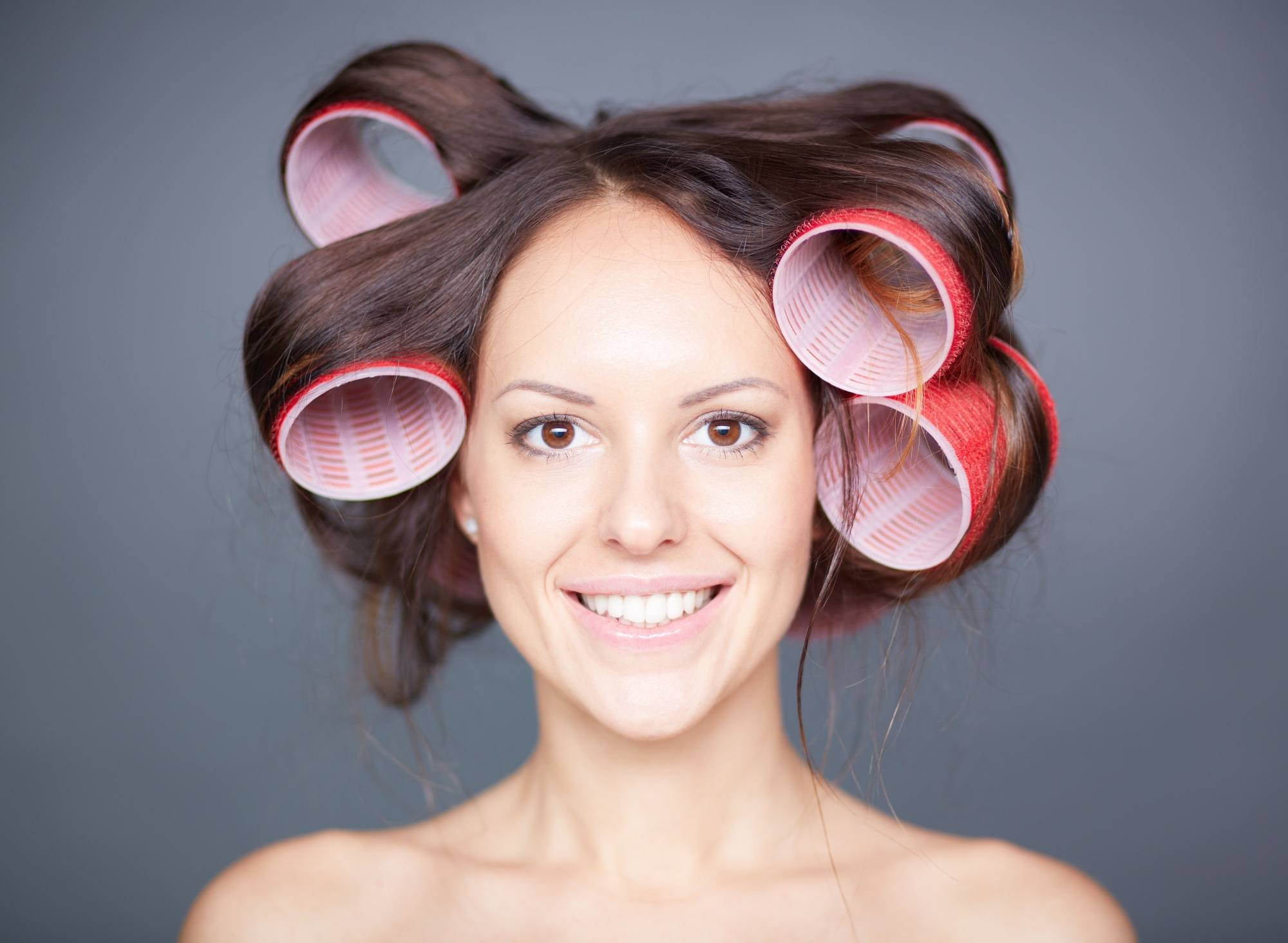 Woman with jumbo rollers on her hair as a natural hair straightener