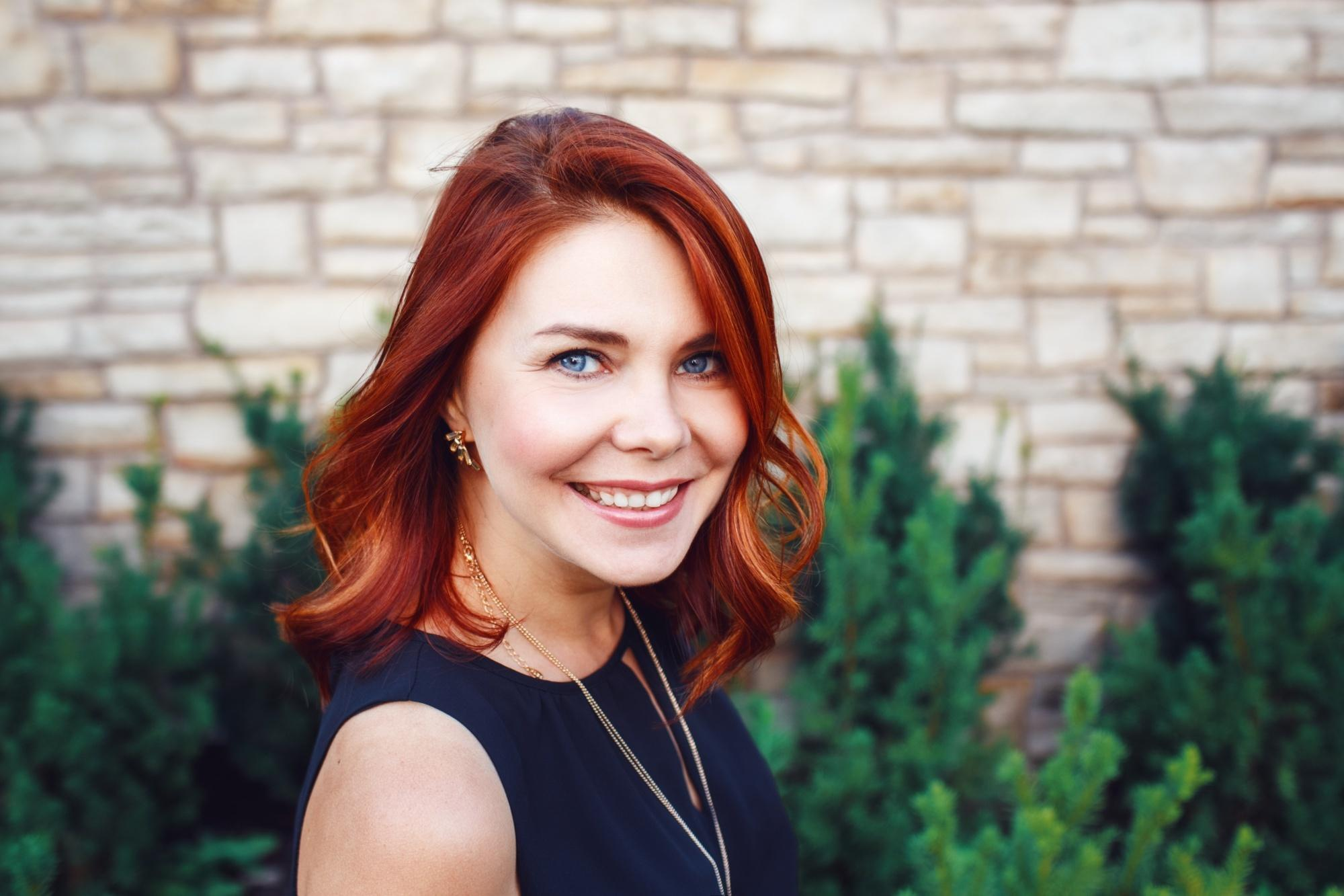 Copper hair color: woman with red toned copper hair smiling at the camera