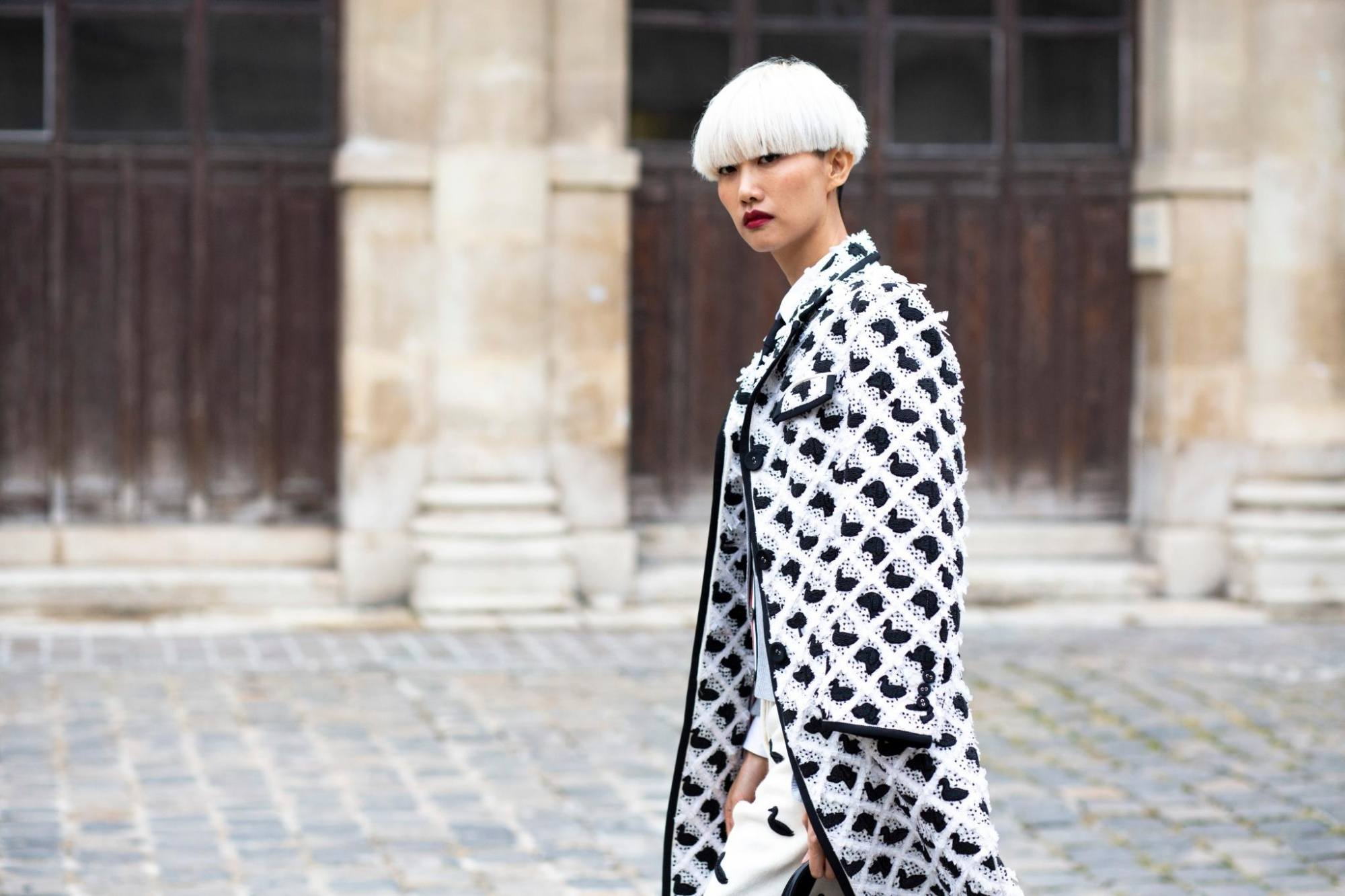Woman with blonde bowl cut short hair wearing a checkered coat outdoors