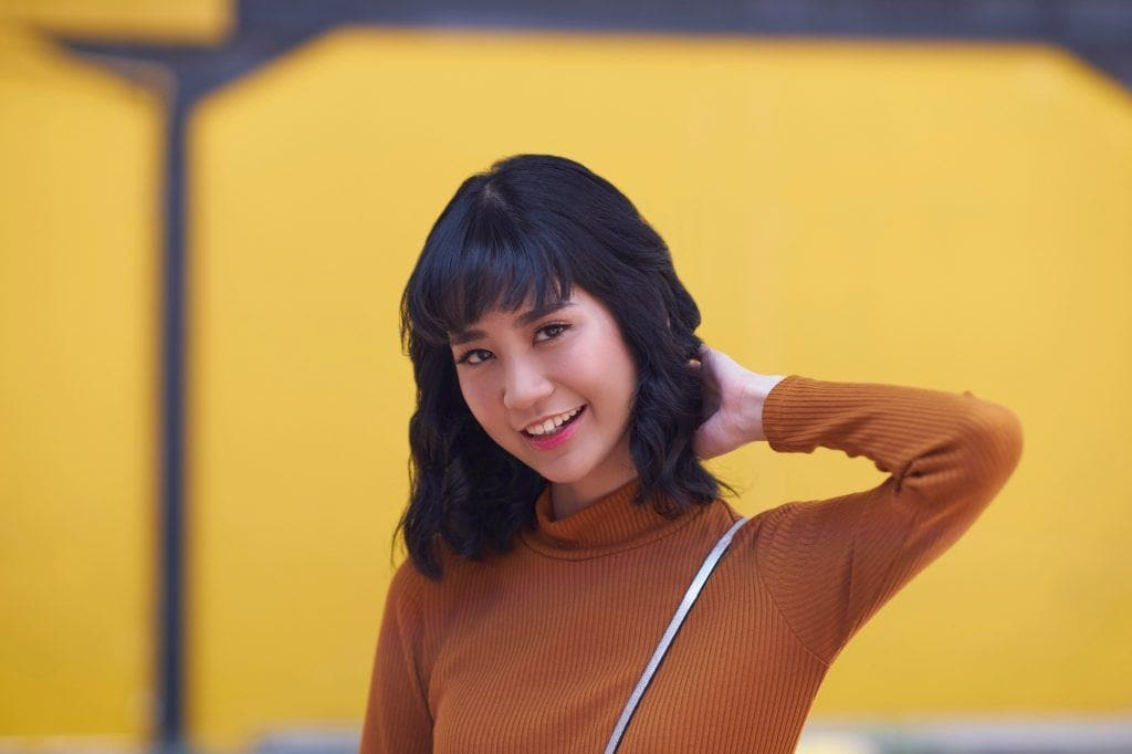 Asian woman with short curly hair with blunt bangs wearing a brown top smiling