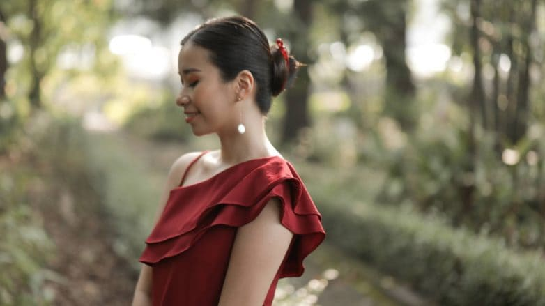 Asian woman wearing a red dress with hair in a banana clip bun standing outdoors