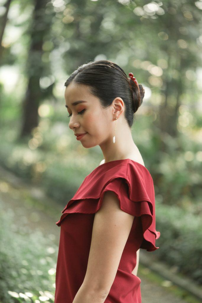 Asian woman wearing a red dress with long hair in a banana clip bun standing outdoors