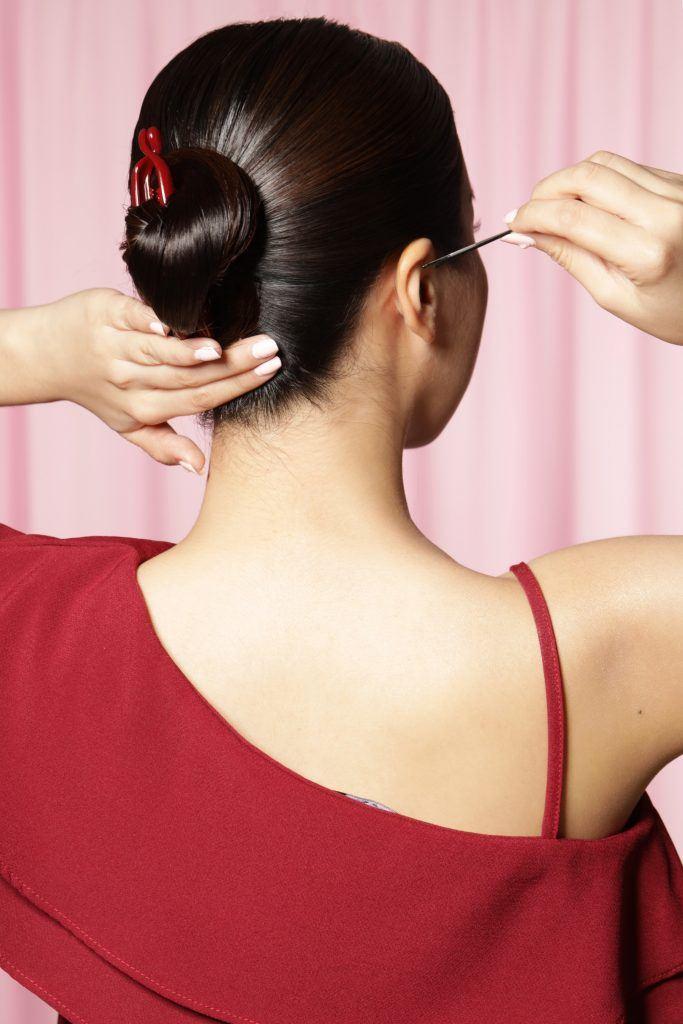 Back shot of an Asian woman wearing a red top pinning her banana clip bun