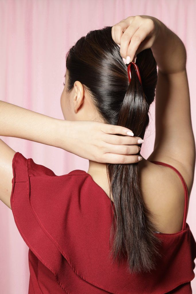 Back shot of an Asian woman putting her long hair in a ponytail using a banana clip