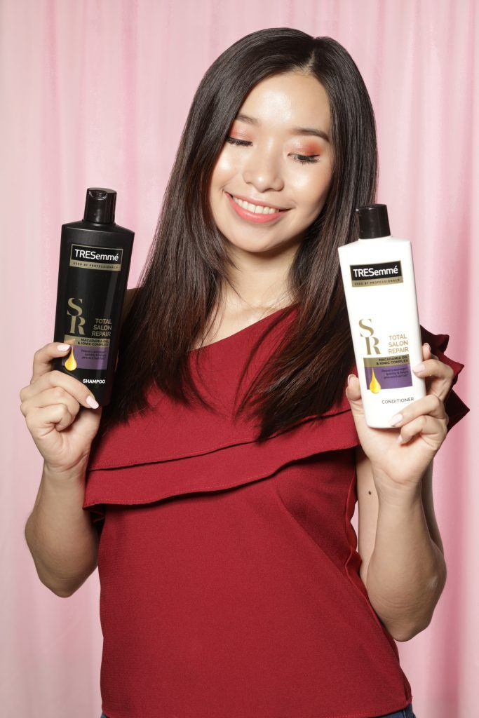 Asian woman with long dark hair holding bottles of shampoo and conditioner