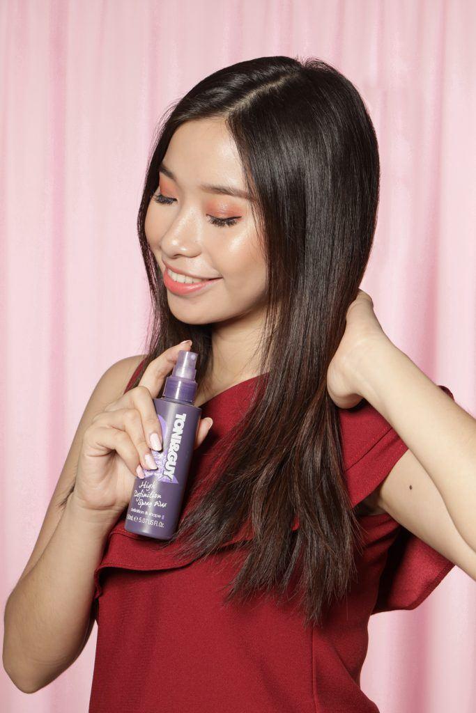 Asian woman spraying hair wax on her long dark hair