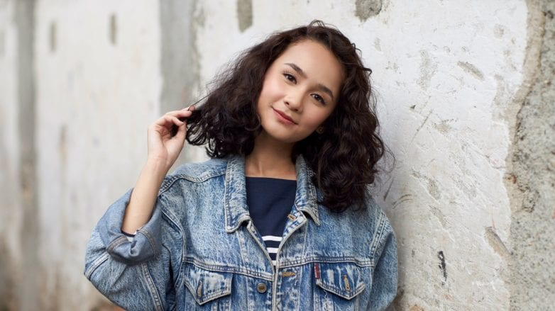 Asian woman with shoulder-length curly hair wearing a denim jacket outdoors
