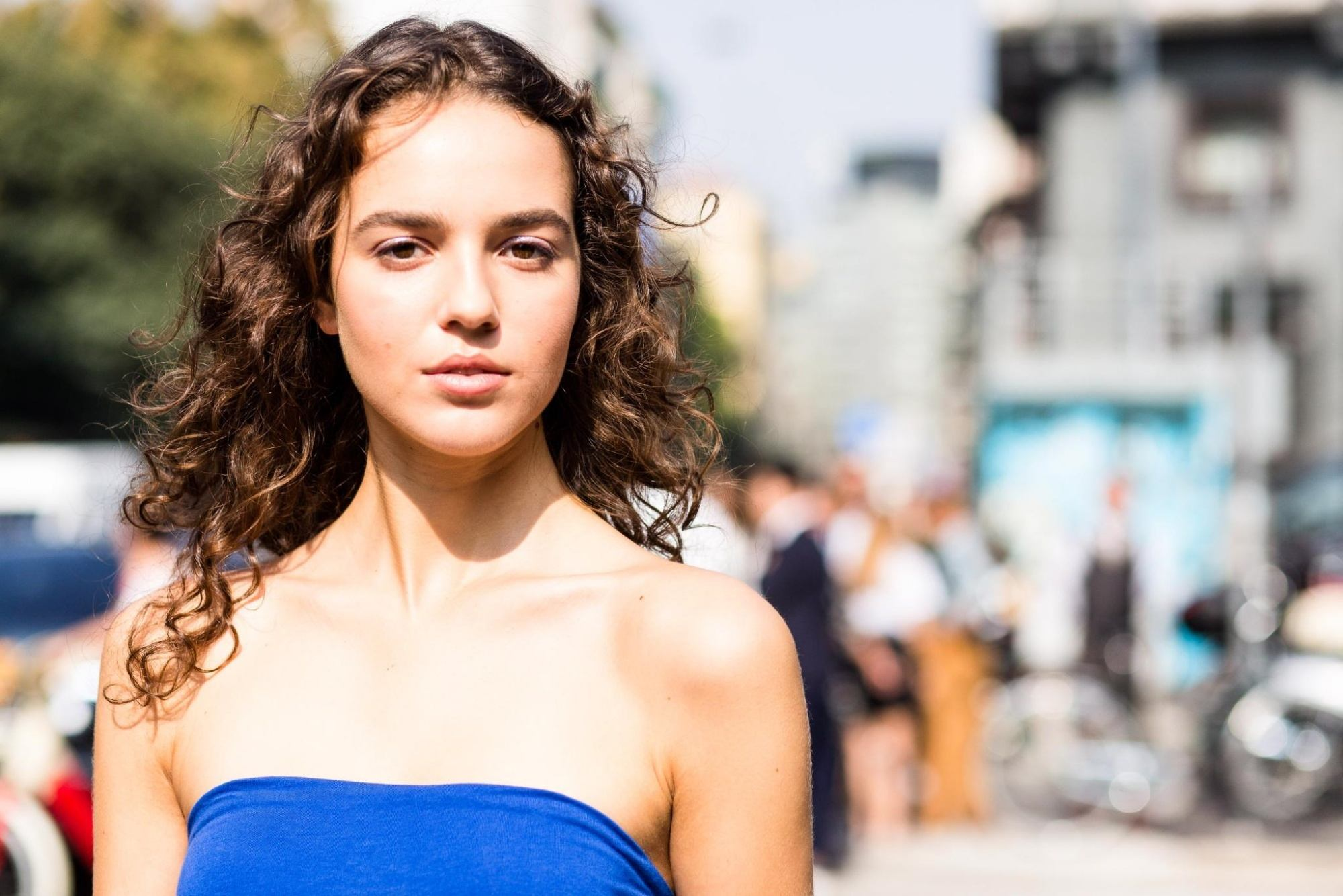 Caucasian woman with long brown curly hair wearing a blue tube top outdoors