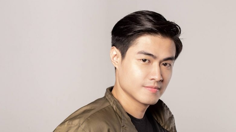 Dandruff Prevention: Asian man with dandruff-free black hair wearing a black shirt and bomber jacket