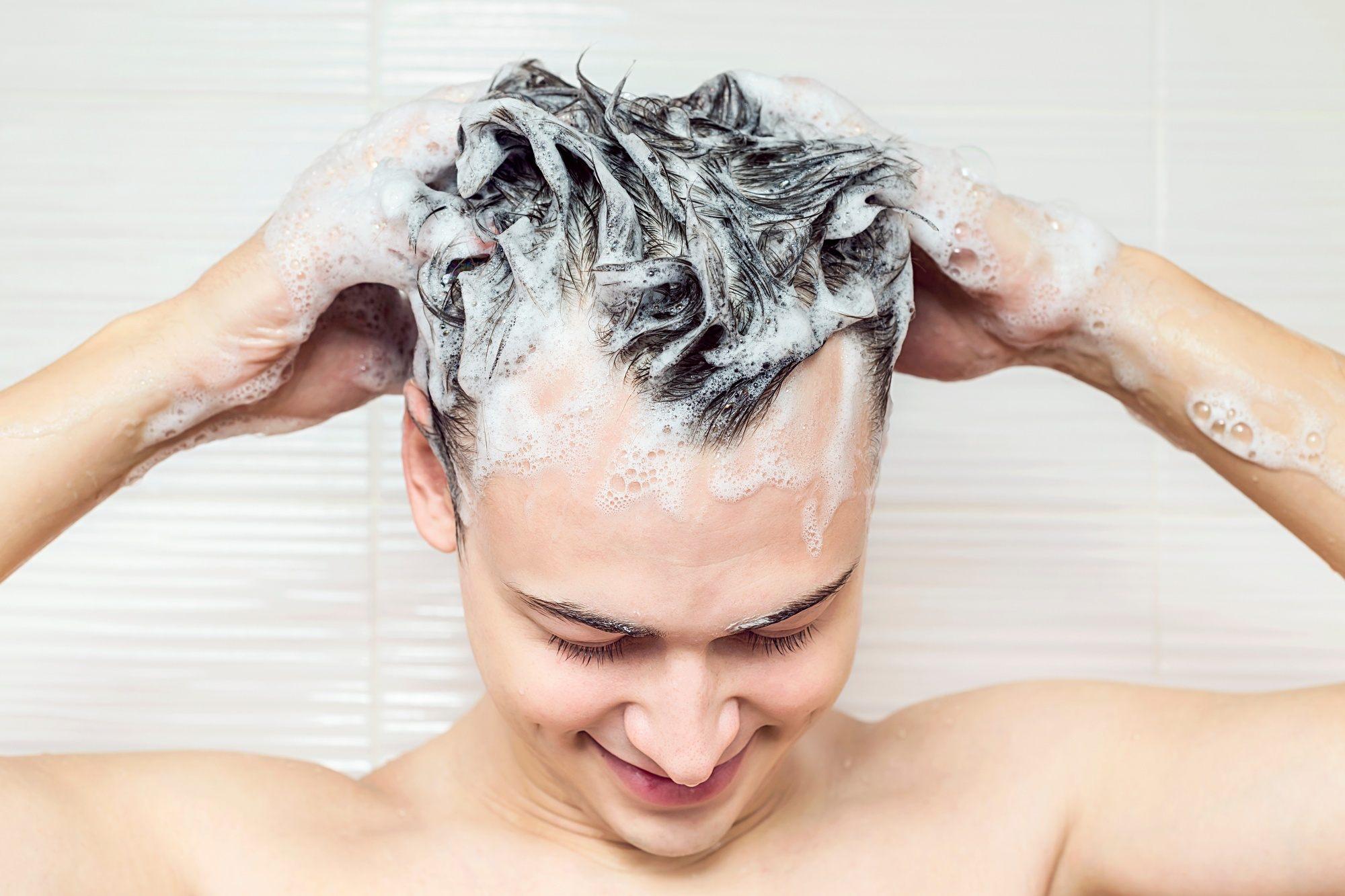 Closeup shot of a Caucasian man shampooing his hair