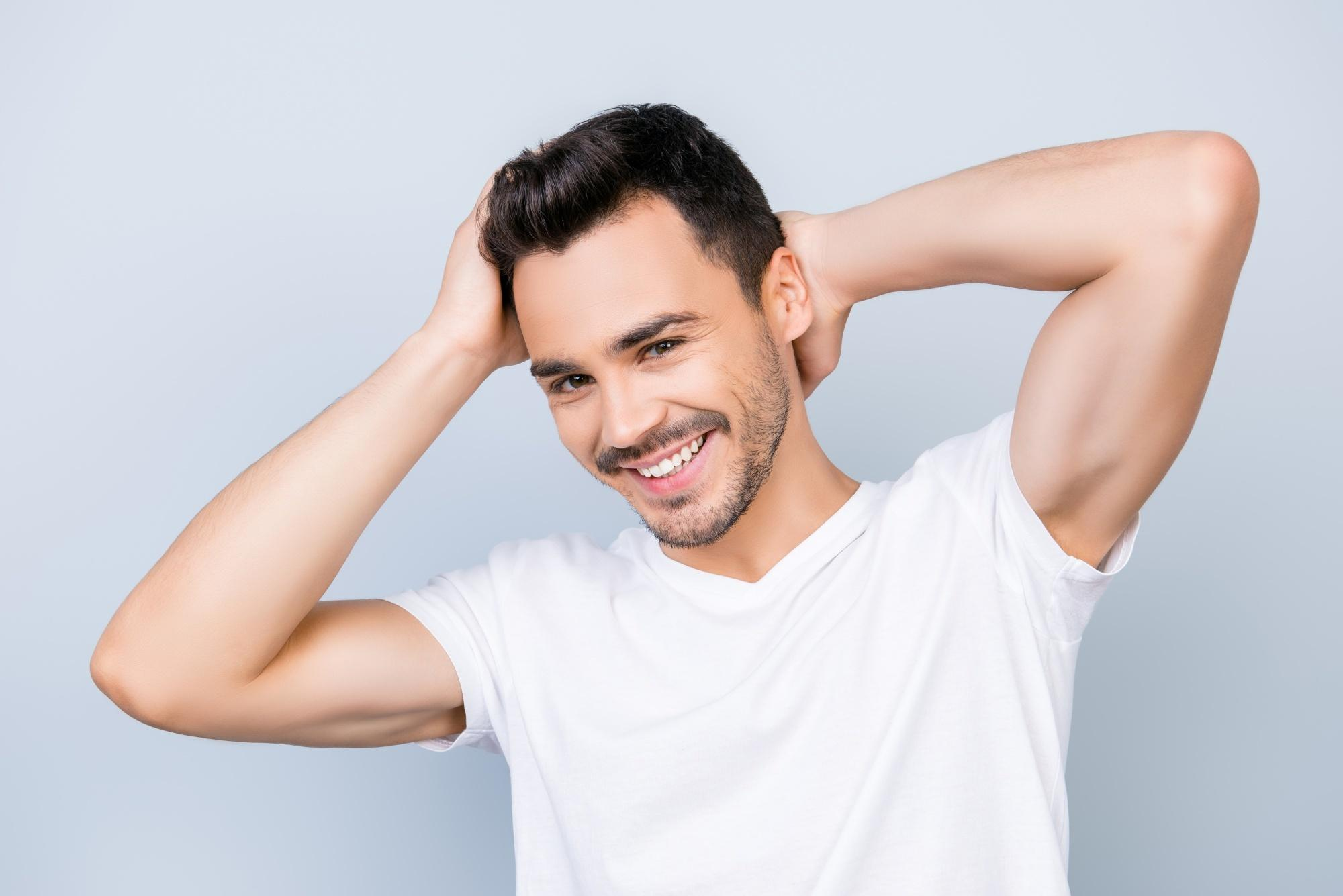 Man wearing a white shirt stroking his dark hair and smiling