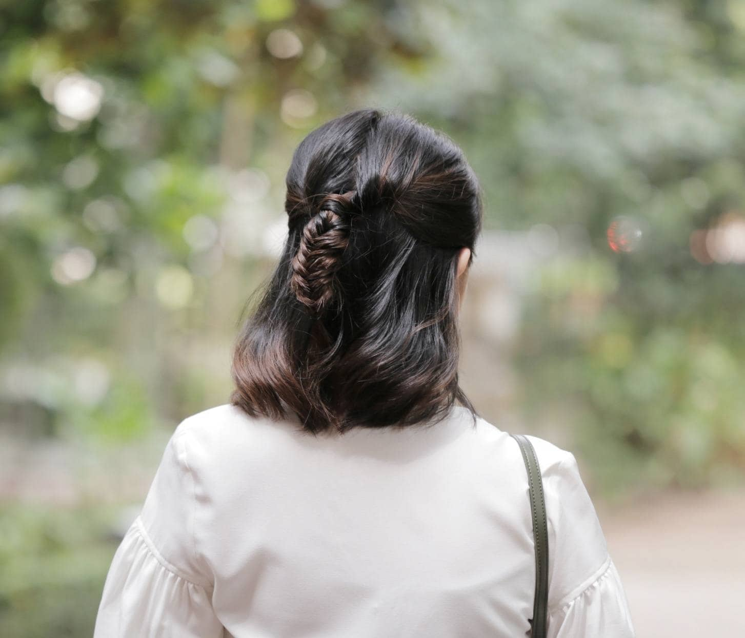 Back shot of an Asian woman with short hair in a half-up fishtail braid