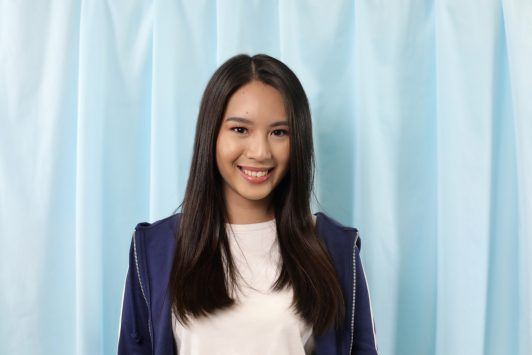 Asian woman with long black hair smiling and wearing a white shirt and dark blue jacket