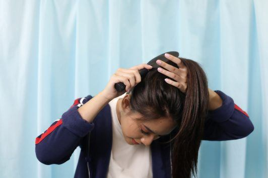 Asian woman with her head forward gathering her hair on her crown using a brush