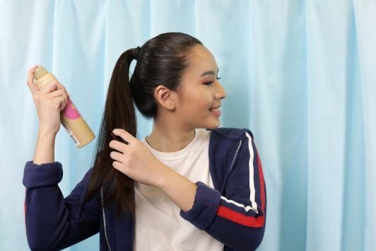 Asian woman spritzing hairspray on her high ponytail