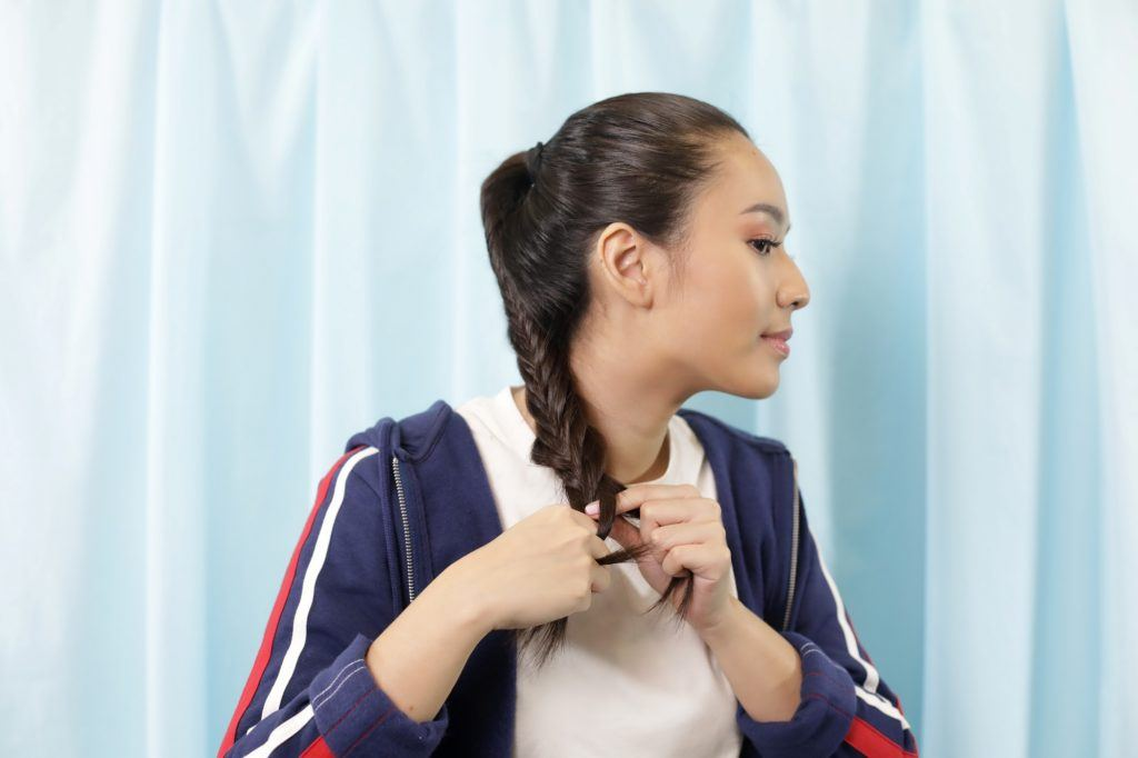 Asian woman tying the tips of her fishtail braid ponytail with an elastic