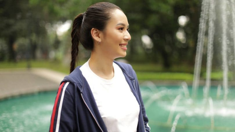 Asian woman with long hair in a fishtail braid ponytail wearing a jacket and smiling in front of a fountain