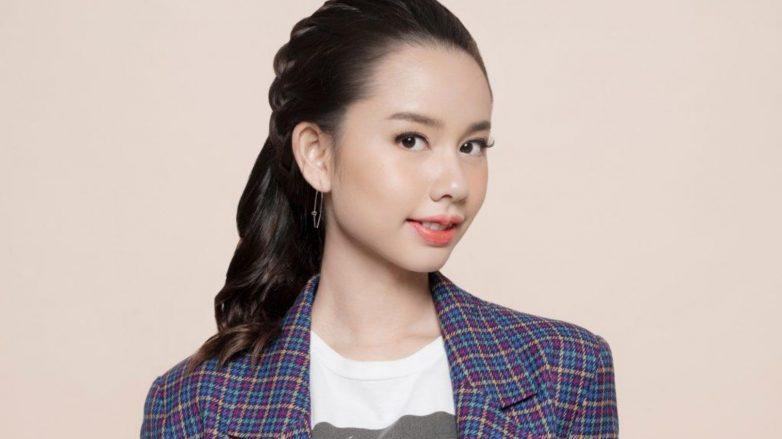 Hair braiding: Asian woman sporting her headband braid, wearing a shirt and a plaid coat