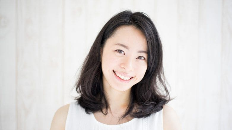 Haircut at home: a smiling Asian woman with beautiful hair, wearing a white top
