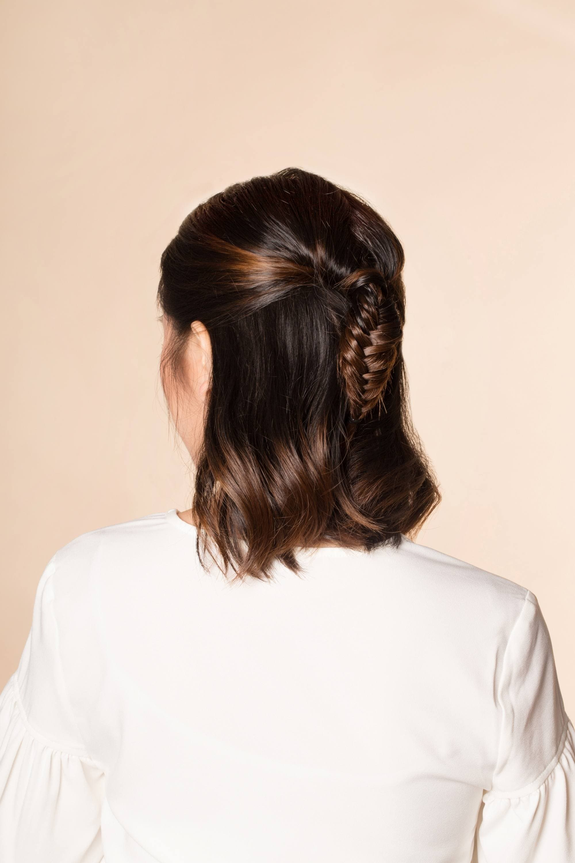 Back shot of an Asian woman with short hair in a half up fishtail braid hairstyle