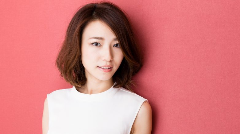 Asian woman with short brown hair wearing a white top as feature for Korean hair care