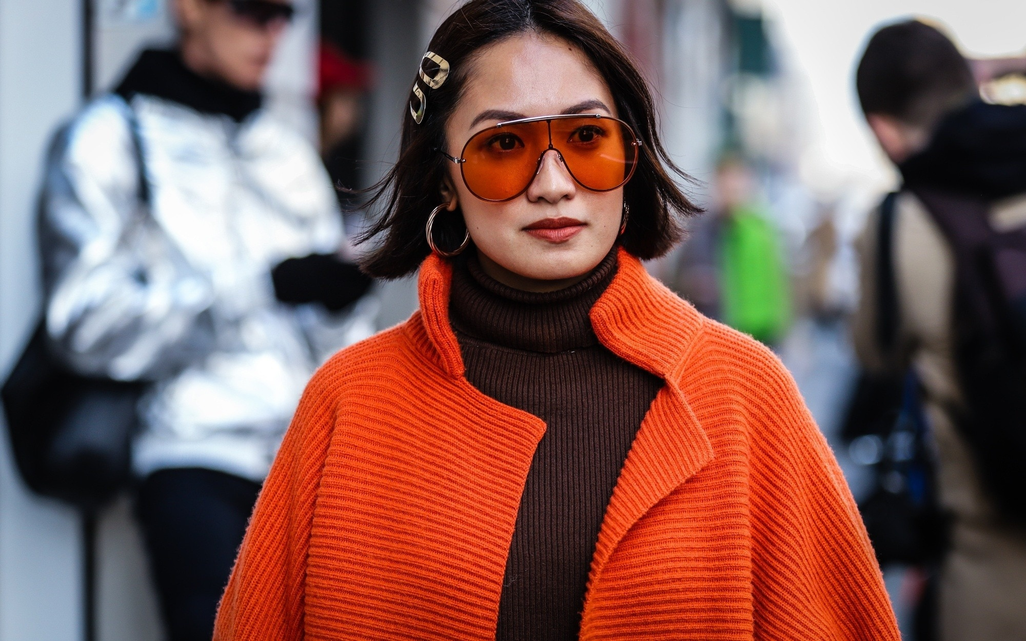 Laureen Uy wearing an orange coat and sunglasses with hair clips on her short hair
