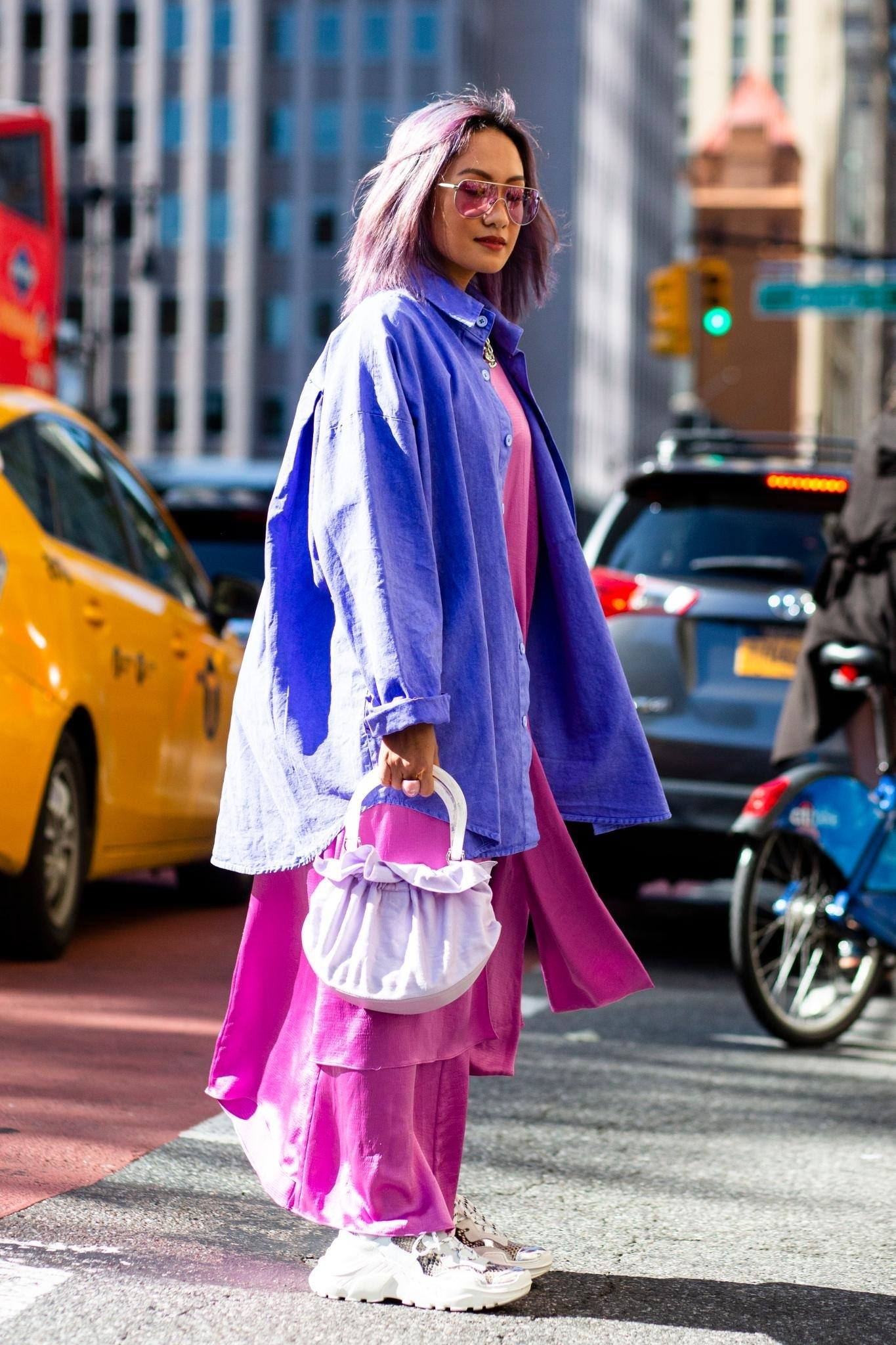 Laureen Uy with purple hair wearing a blue jacket and pink dress shot street style at NYFW SS 2020