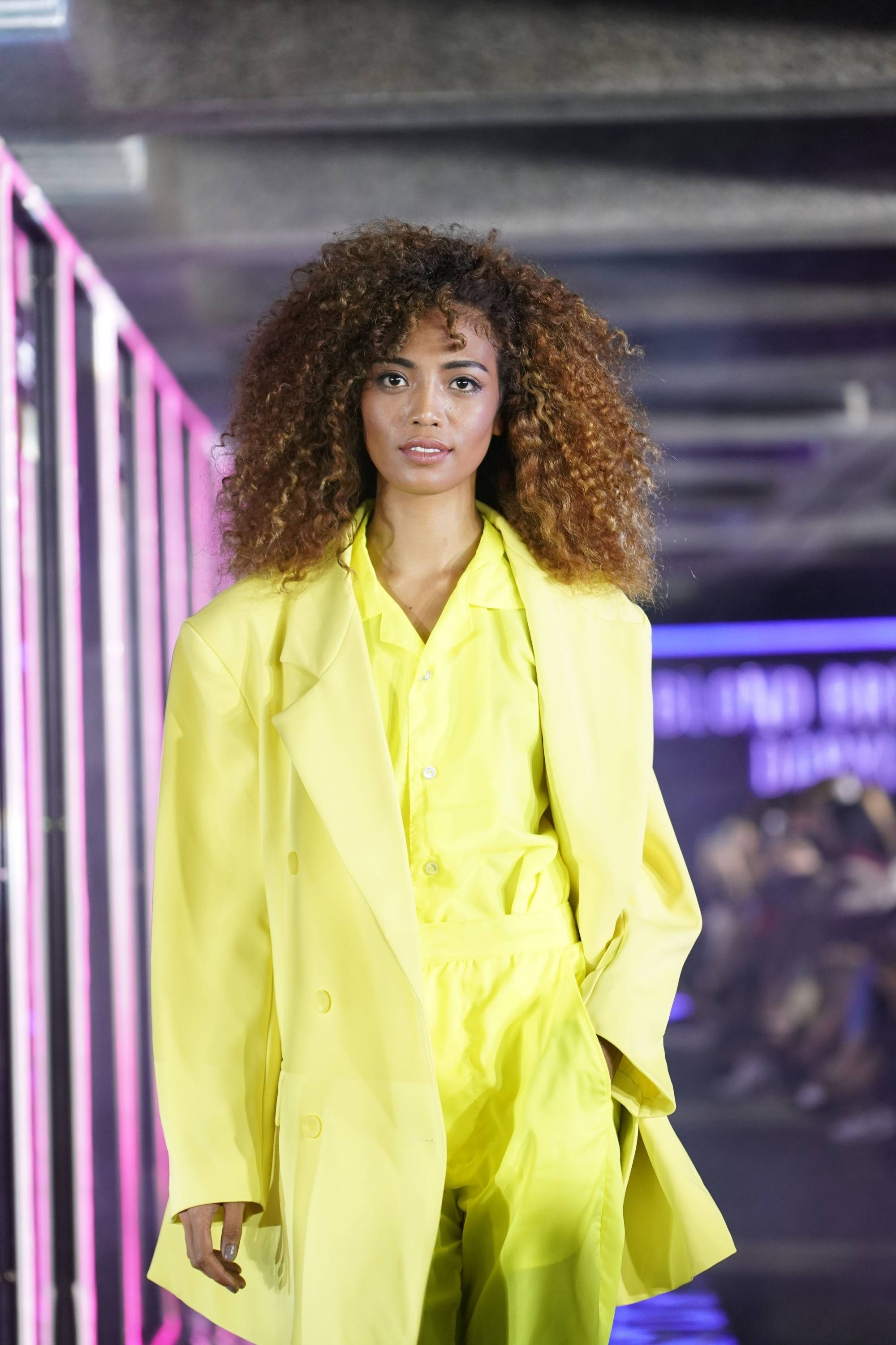 TRESemme Runway 2019: model with chocolate toned curly hair in a yellow pantsuit