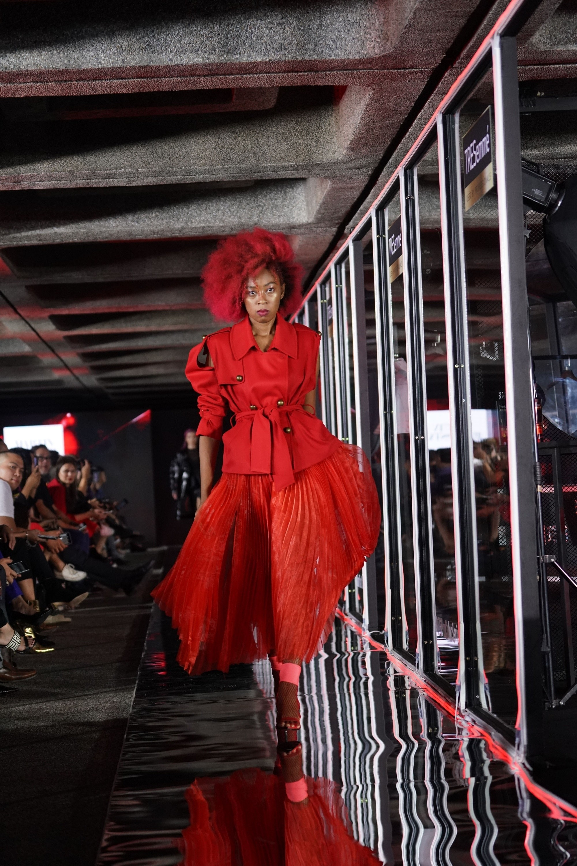 A model with big red hair wearing a red top and skirt