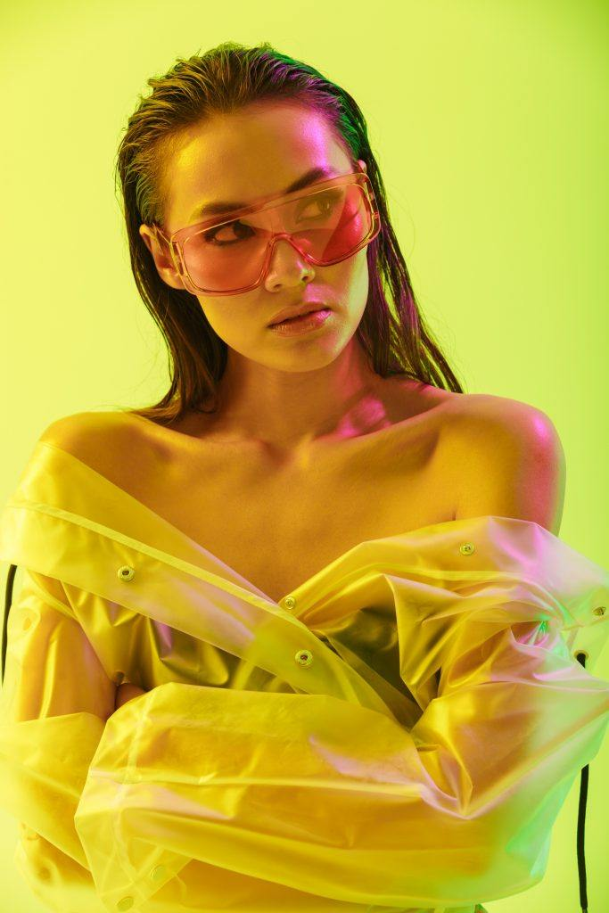 Wet hair look pegs: woman with slicked back hair, wearing a raincoat off her shoulders and a pair of shades