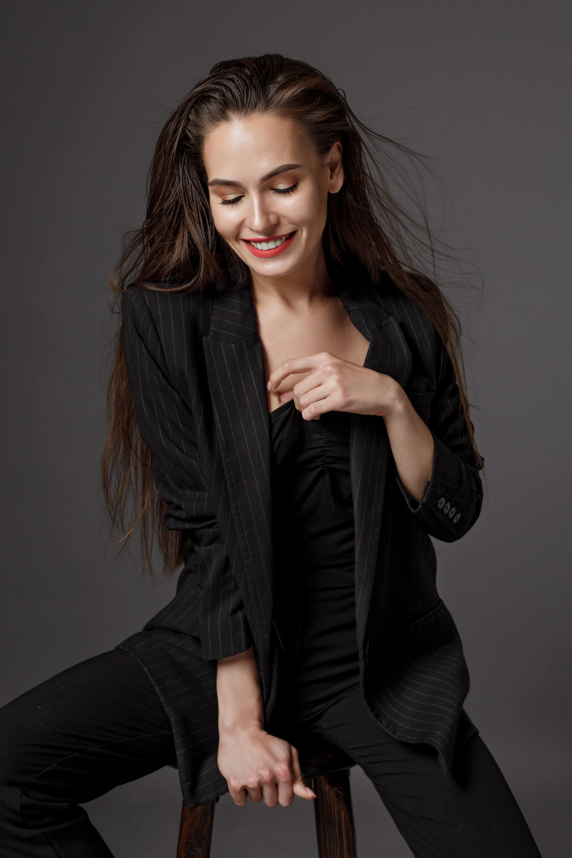 Wet hair look pegs: woman in a black pantsuit, sporting her tousled wet hair while sitting